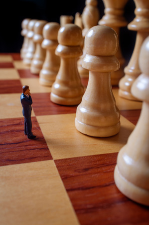 Miniature businessmen battle with giant chesspieces for symbolic metaphor