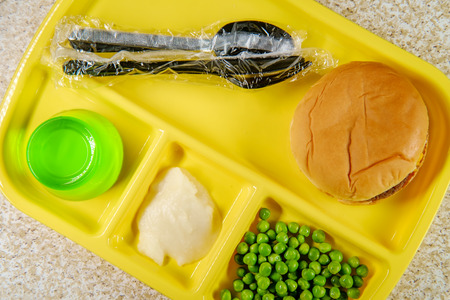 Elementary school lunch cheeseburger with mashed potatoes jelly  and green peas on portion tray