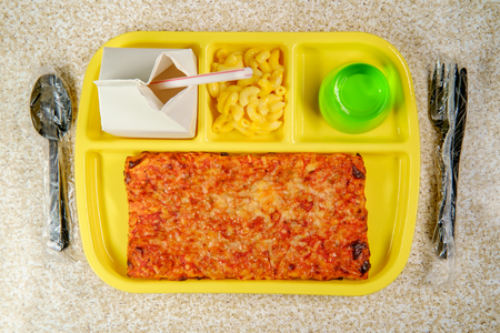 Grade school lunch tray with pizza with small carton of milk mac-n-cheese and green jelly for dessert