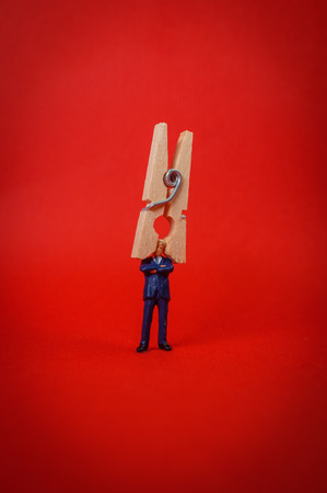 Businessman with clothespin on head symbolizing ignorance and refusal to listen
