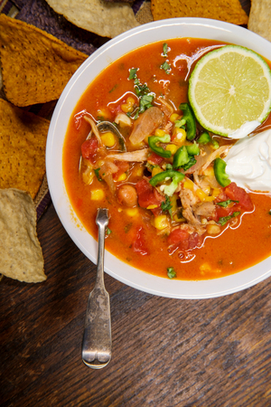 Hearty and spicy tortilla soup with hot peppers and orange purple and white multicolored torttilla chips