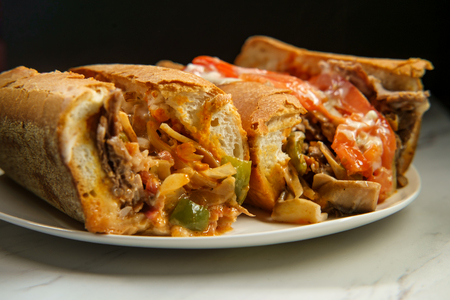 Messy buffalo cheesesteak sandwich with sliced tomatoes and a rich creamy bleu cheese sauce