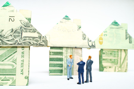 Miniature figurine businessmen and origami paper money houses for real estate and housing market concept