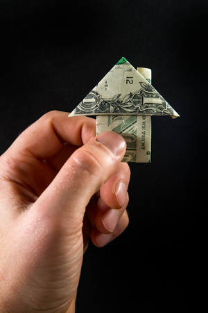 Hand holds origami paper money house for real estate and housing market concept Stok Fotoğraf