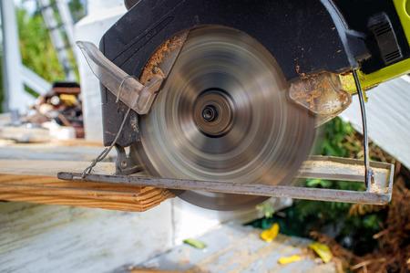 Old worn circular saw power tool cutting wood