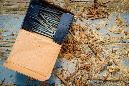 Box of contracting deck screws with sawdust on worn wooden porch Stock Photo