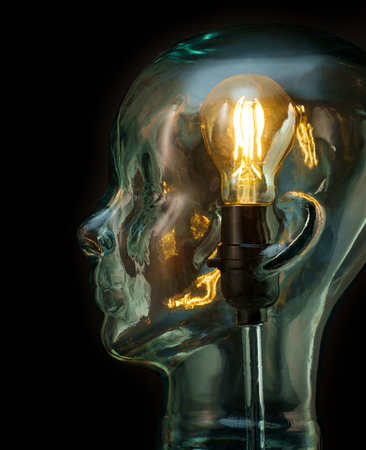 Bright lightbulb inside glass head for creative thoughts and ideas concept