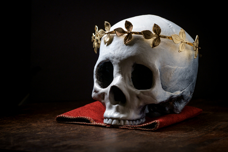 Human skeleton skull of King or Queen wearing royal gold leaf crown Standard-Bild - 112361752