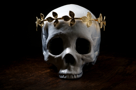 Human skeleton skull of King or Queen wearing royal gold leaf crown Фото со стока - 112361756