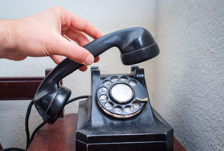 Old vintage rotary dial telephone on wooden desk Stock Photo
