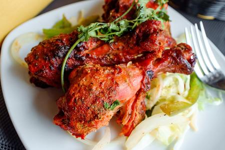 Indian cuisine spicy Tandoori chicken with cilantro garnish Stock Photo