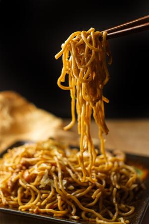 Jedzenie chińskiego makaronu wieprzowego lo mein z pałeczkami