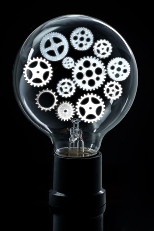 Light bulb with bright gears and cogs for brainstorming ideas concept