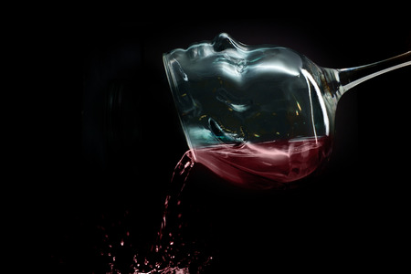 Wine glass has a face as though the wine takes the place of the addicts brain