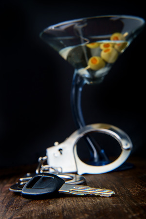 Gin martini with handcuffs and keys symbolizing drunk driving arrest