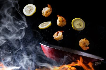 Revuelva freír y arrojar camarones con concepto de limón en rodajas con humo de vapor y llamas