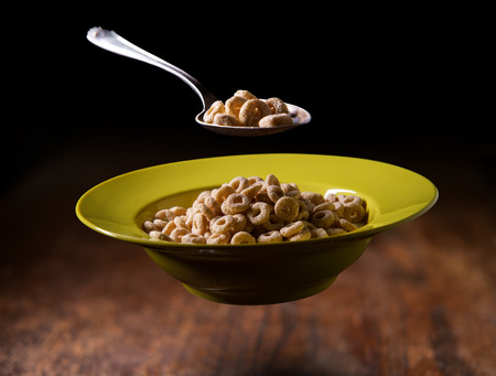 Bowl of oat cereal rings floating in the air traditional American breakfast concept Stok Fotoğraf