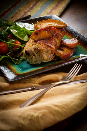Bacon wrapped pork with dijon mustard and baked apple slices Foto de archivo - 112360379