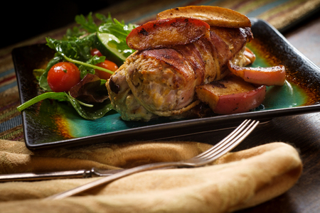 Bacon wrapped pork with dijon mustard and baked apple slices Stock Photo