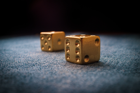 Lucky golden gambling dice on blue green billiards table Stok Fotoğraf