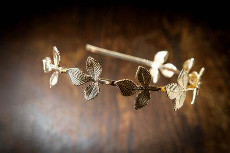 Golden laurel leaf Greek or Roman crown on dark moody wooden table Standard-Bild - 112360242