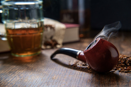 Leisure tobacco pipe and whisky with bottle and a good mystery book Foto de archivo
