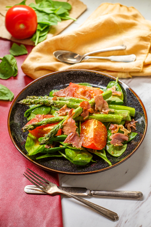 Prosciutto asparagus salad with roasted tomatoes spinach leaves and balsamic vinaigrette