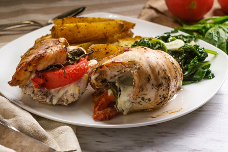 Caprese stuffed chicken with garlic broccolini and steak fries Imagens