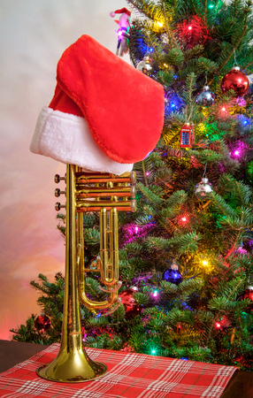 Seasonal holiday musical instrument trumpet with Christmas tree background