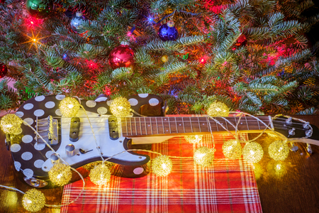 Seasonal holiday musical instrument ukulele with Christmas tree background