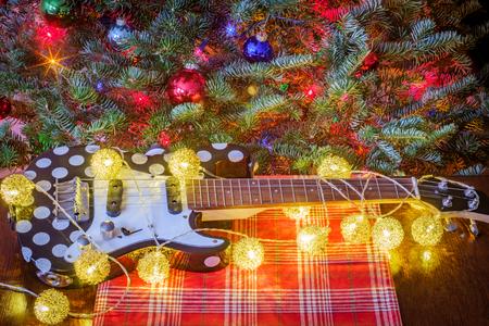 Seasonal holiday musical instrument ukulele with Christmas tree background