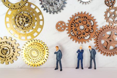 Empresarios rodeados de engranajes y ruedas dentadas para la metáfora conceptual de la innovación Foto de archivo