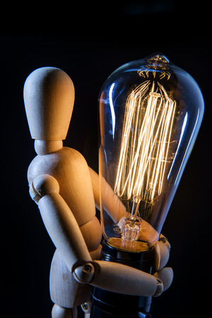 Wooden articulated artist doll holding antique edison light bulb Banco de Imagens