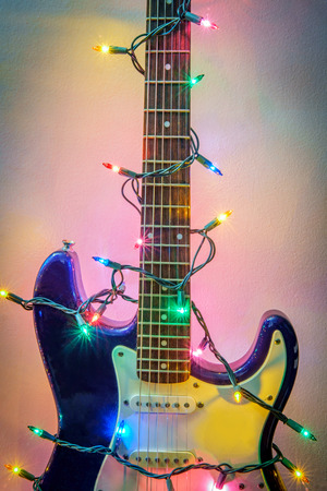 Seasonal holiday musical instrument electric guitar wrapped in Christmas tree string lights