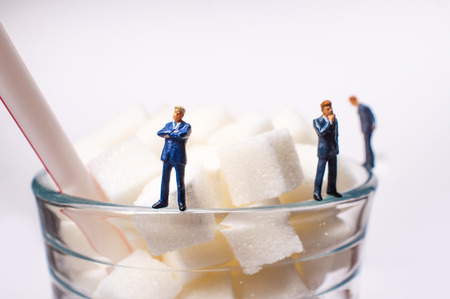 Conceptual sugar cubes in glass with striped soda straw and businessmen diabetes conceptual metaphor Reklamní fotografie