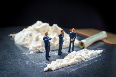 Drug addiction conceptual metaphor miniature businessmen doing giant line of cocaine