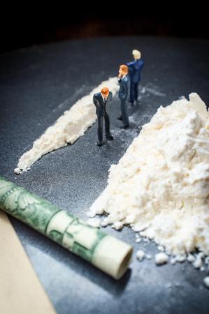 La adicción a las drogas metáfora conceptual empresarios en miniatura haciendo una línea gigante de cocaína Foto de archivo
