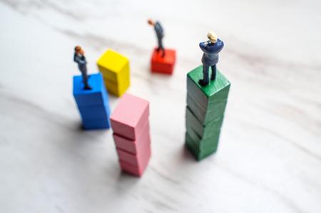 Miniature businessmen stand on wooden blocks symbolizing steps to success Banque d'images
