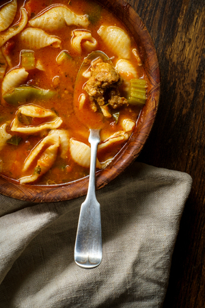Hearty Italian minestrone soup with sausage in wooden bowl