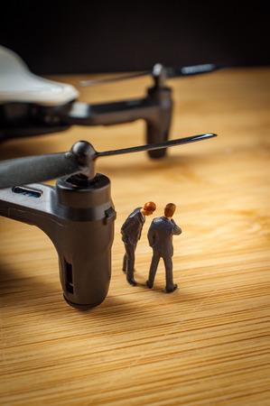 Closeup macro miniature businessmen figurines with drone quadcopter 写真素材