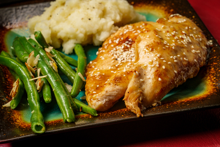 Honey sesame chicken teriyaki fusion with sliced almond green beans and mashed potatoes 版權商用圖片