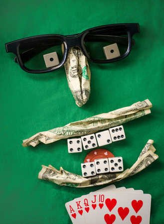 Silly bad poker face metaphor made from various gambling items including money dice cards and poker chips 스톡 콘텐츠