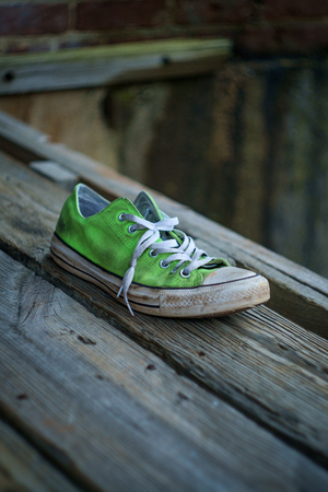 Old smelly worn classic sneaker lost on city street Stok Fotoğraf