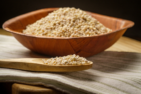 Dry raw uncooked pearled barley in a wooden bowl
