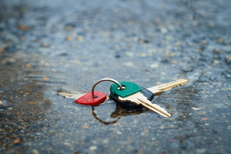 Rainy day lost car keys in wet parking lot pavement Archivio Fotografico