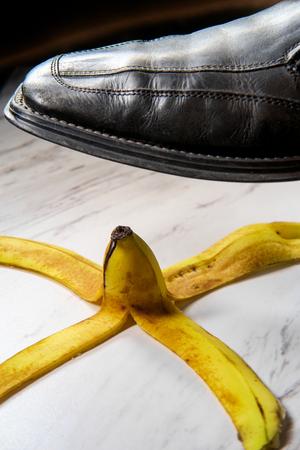 Business man stepping on comedy slippery banana peel