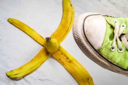 Classic slippery comedy banana peel with sneaker about to step on it Stock Photo