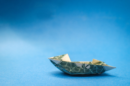 Miniature money dollar bill origami yacht conceptual metaphor