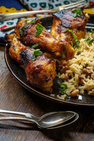 African cuisine grilled chicken legs with jollof rice with orzo and black eyed peas