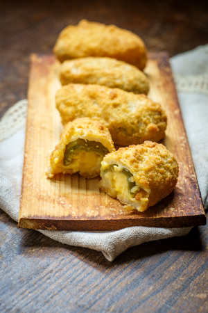 Crispy fried cheddar cheese jalapeno popper bites served on wooden cedar plate with dark moody lighting Stock Photo